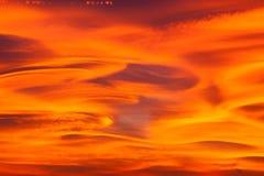 与双突透镜的云彩的美丽的日落天空 免版税库存图片