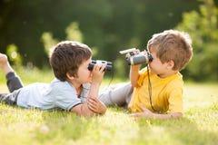 与双筒望远镜的两个孩子戏剧 免版税库存图片