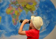 与双筒望远镜的孩子充当旅客 冒险和旅行概念 创造性的背景 免版税库存照片