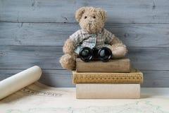 与双筒望远镜的玩具熊坐堆旧书 库存照片
