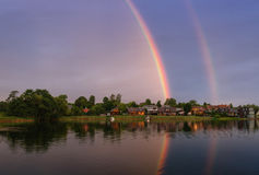 与双重彩虹的镇静夏天风景在湖、蓝天和小船上 免版税库存图片