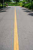 与双黄线分切器的沥青路在阳光下 图库摄影