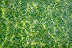 与反射光线的波纹在游泳池绿色马赛克底部的  免版税库存照片