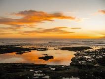 与反射在海洋的云彩的五颜六色的日落 免版税图库摄影