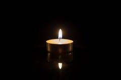 与反射的一个茶蜡烛在黑色 库存照片