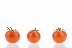 与反射的三个西红柿,在白色 免版税库存图片