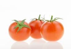 与反射的三个西红柿,在白色 库存图片