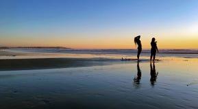 与反射的令人敬畏的冲浪者日落 免版税库存照片