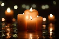 与反射的四个灼烧的蜡烛 库存照片
