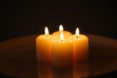 与反射的蜡烛在一块白色板材 免版税库存照片