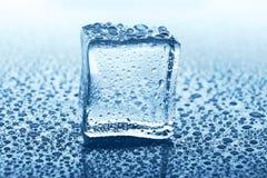 与反射的透明冰块在蓝色玻璃用水滴下 图库摄影