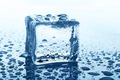 与反射的透明冰块在蓝色玻璃用水滴下 免版税图库摄影