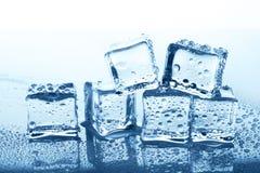 与反射的透明冰块小组在蓝色玻璃用水下降 库存照片
