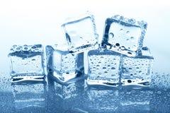 与反射的透明冰块小组在蓝色玻璃用水下降 免版税库存照片