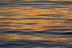 与反射背景的日落颜色的起波纹的水 库存图片