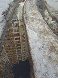 与反射高层建筑物,与脚印人鞋子版本记录的熔化的雪的水坑的雪道轨道  库存照片