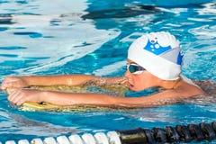 与反撞力委员会的男孩游泳 免版税库存照片