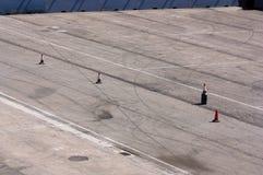 与发信号路的锥体的涂柏油的区域跟随汽车 库存图片