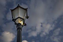 与发光在一个古色古香的街灯postThe中世纪欧洲灯岗位的一块残破的玻璃的一个白炽电灯泡被做熔铸st 免版税库存图片