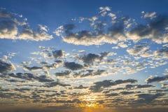 与发光在通行证云彩和天空下的光的日落天空 免版税库存照片