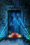 与发光的一个邪恶笑的鬼的可怕橙色南瓜在公墓前面注视在晚上 免版税库存照片