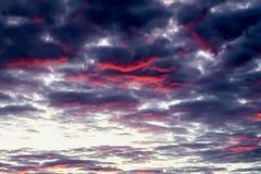 与发光的充满活力的云彩的意想不到,但是真正的惊人的多色日落在剧烈的五颜六色的天空 美丽织地不很细 免版税库存照片