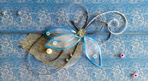 与发光的小珠、刺绣、银色螺纹以花的形式和蝴蝶的蓝色水平的手工制造问候装饰 库存照片