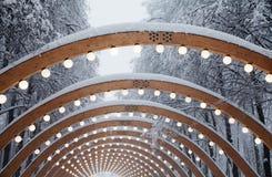 与发光的电灯泡的积雪的曲拱 美好的冬天季节几何风景 免版税库存照片