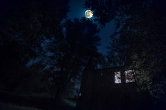 与发光的窗口的农村哥特式城堡在夜空的黑暗的森林里与月亮 免版税库存图片