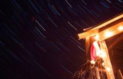 与发光的诗歌选和圣诞老人帽子在满天星斗的天空的背景,在夜空的星轨道的圣诞节背景, 图库摄影