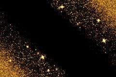 与发光的金子闪烁在黑背景发火花 库存图片