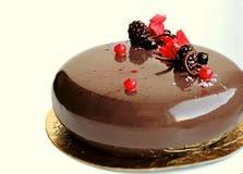与发光的镜子釉的在白色背景的巧克力蛋糕和莓果 免版税库存图片