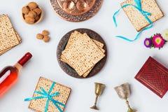 与发酵的硬面、酒和seder板材的犹太逾越节假日Pesah庆祝概念在白色背景 在视图之上 平的l 免版税库存照片