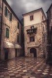 与古老石摊铺机的葡萄酒中世纪正方形有中世纪建筑学的在老欧洲城市科托尔在黑山 免版税库存照片