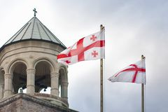 与古老英王乔治一世至三世时期教会和天空的乔治亚旗子在背景中 免版税库存图片