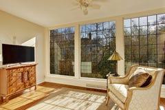 与古色古香的椅子和电视的明亮的日光浴室 免版税库存图片