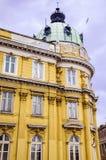 与古色古香的窗口和屋顶的老石橙色大厦 免版税图库摄影