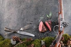 与古色古香的长的枪、利器和成份的鹿或鹿肉牛排喜欢海盐、草本和胡椒, restaura的食物背景 免版税图库摄影