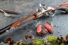 与古色古香的长的枪的鹿或鹿肉牛排和成份喜欢海盐和胡椒、食物背景餐馆的或狩猎lo 免版税库存照片