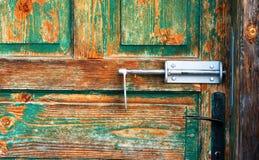 与古色古香的门把手的老绿色木进口 免版税图库摄影