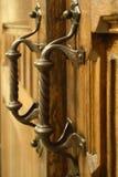 与古铜色扭转的把柄的古色古香的木被雕刻的门 免版税库存图片