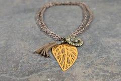 与古铜色链子的古色古香的项链,绿色太阳塑造了垂饰和罐子叶状的垂饰 免版税库存照片