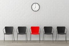 与另一黑色的红色椅子对有现代时钟的墙壁 图库摄影