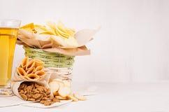 与另外速食快餐和啤酒的柳条土气篮子在白色木背景的葡萄酒杯 库存照片