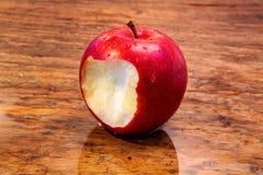与叮咬的红色湿苹果在土气木桌上 免版税图库摄影