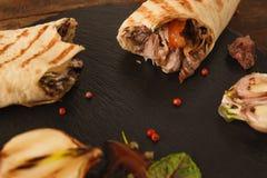 与叮咬的Shawarma被采取在它外面在板材 库存照片