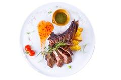 与可口肉片的原始的第二个盘和土豆一道配菜在白色背景的 免版税库存照片