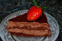 与可可粉奶油和草莓的巧克力蛋糕 免版税库存照片