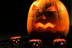 与可怕面孔的万圣夜在眼睛的南瓜和蜘蛛 免版税库存图片
