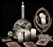 与可怕头骨、灼烧的蜡烛和占卜用的纸牌的静物画在黑色 免版税库存图片